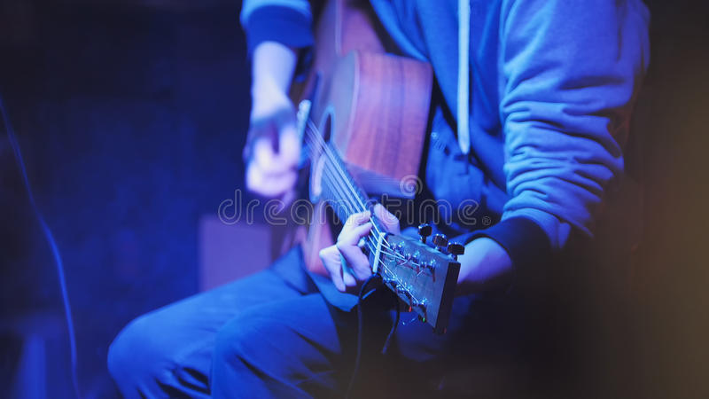 Musician in night club guitarist plays acoustic guitar, close up. Telephoto stock image