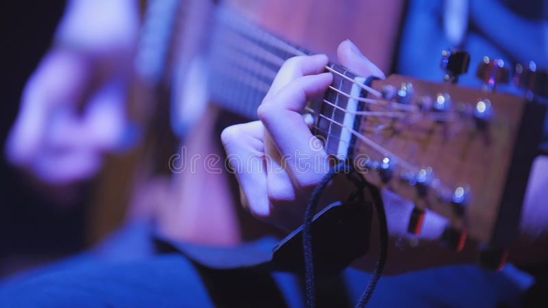 Musician in night club guitarist plays acoustic guitar, extremely close up. Telephoto royalty free stock photos