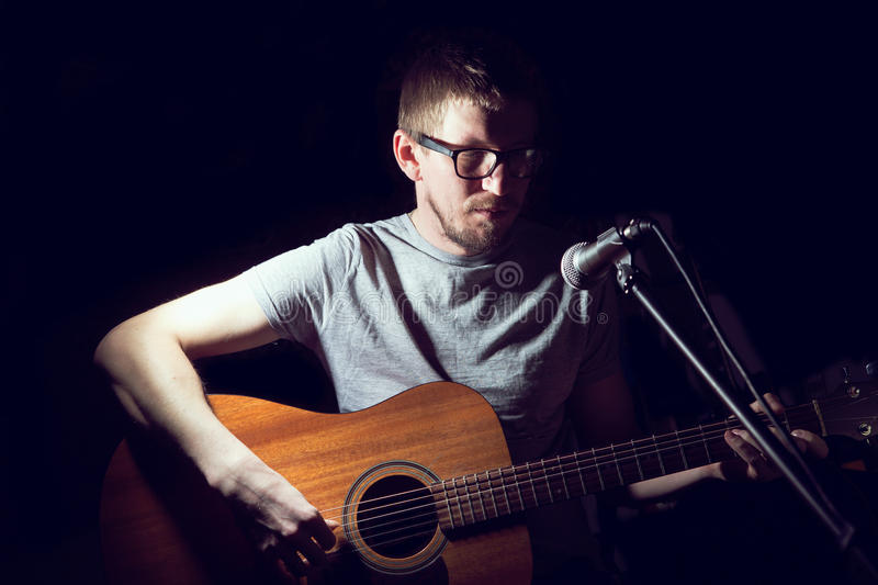 Musician playing acoustic guitar and singing stock images