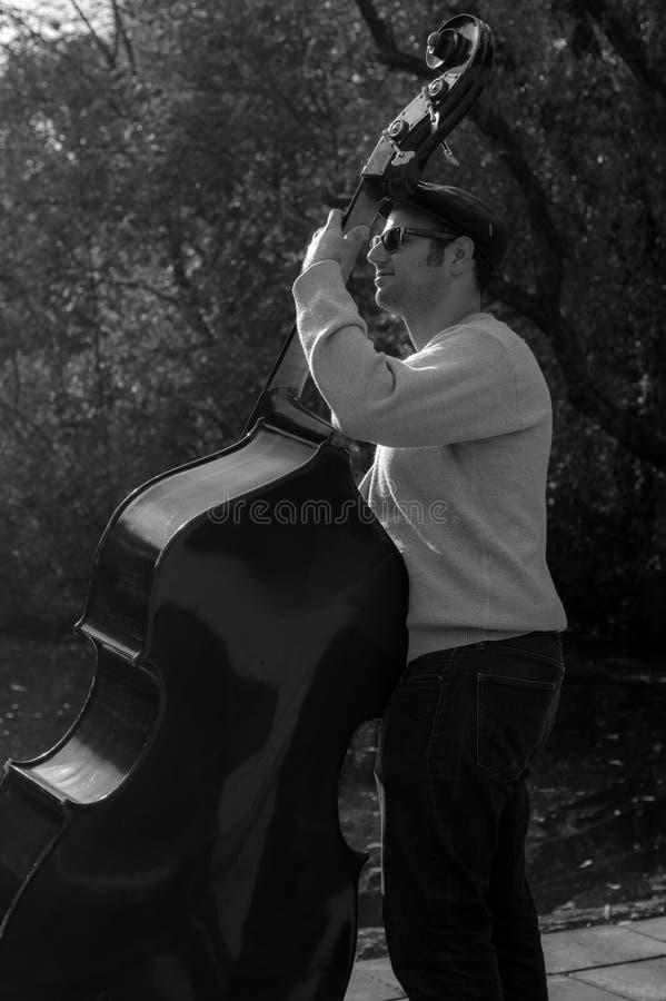 Musician playing bass outdoors stock photos