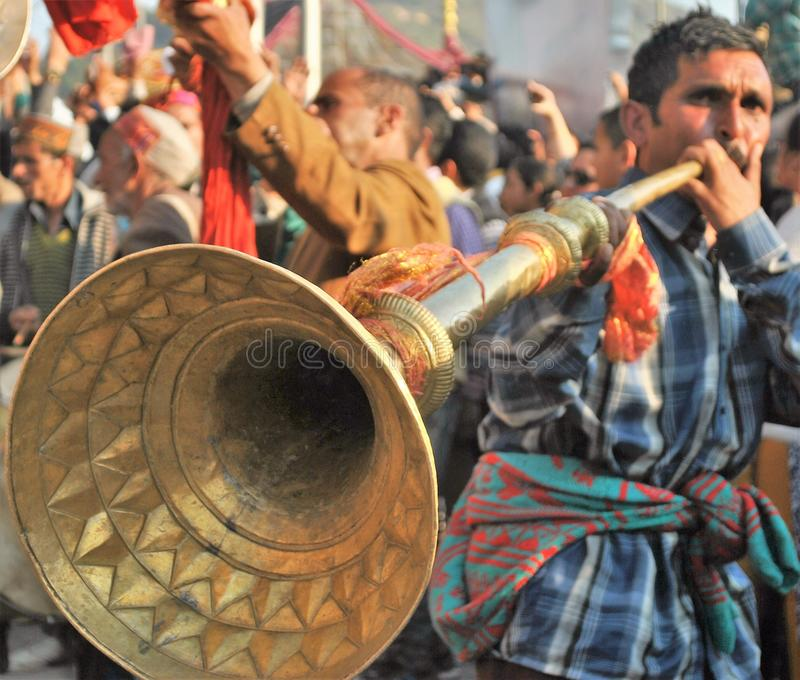 Musician playing Brass Trumpet called karnal - Himachal. Himachali Man playing the Karnal during the Shivratri Fair Procession at mandi royalty free stock photos