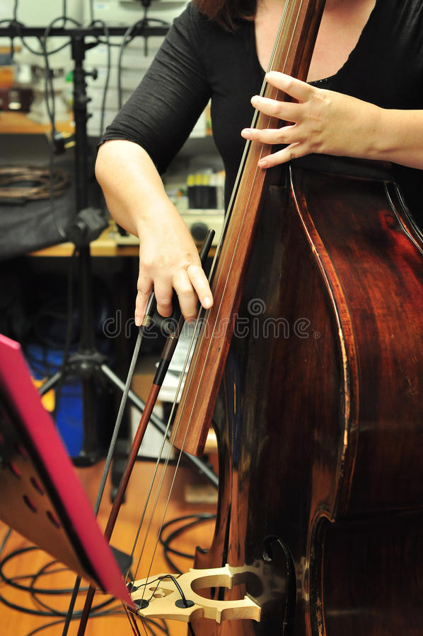 Musician playing cello. Close crop of a female cellist in a recording studio setting stock photography