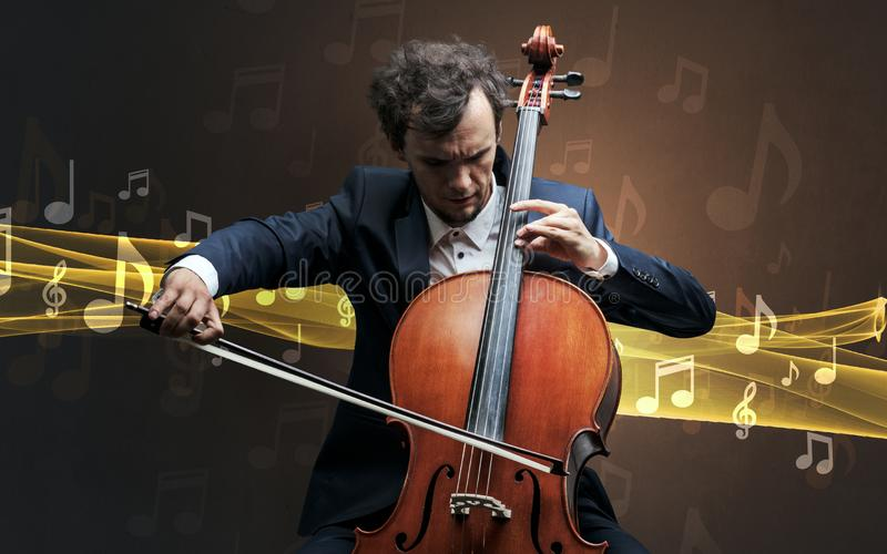 Musician playing on cello with notes around. Young male musician playing on his cello with musical notes around stock photo