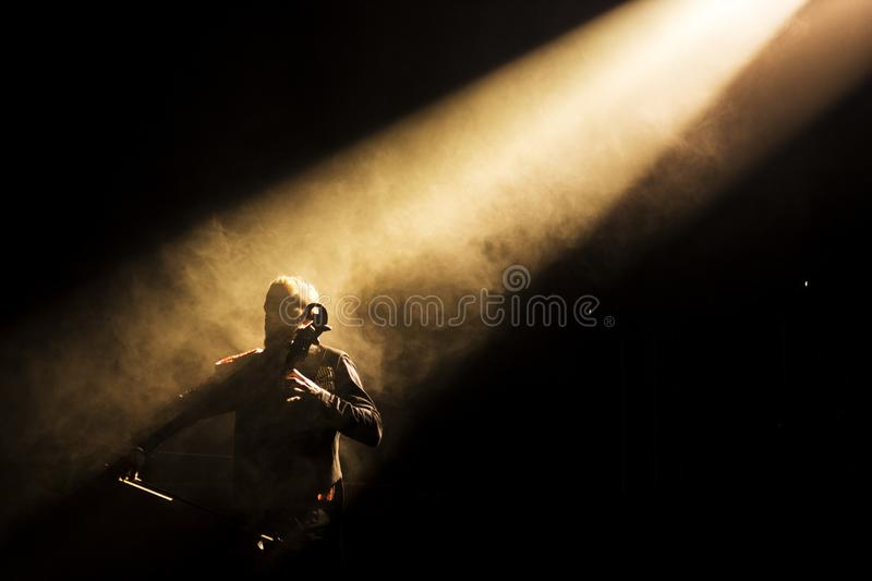 Musician playing double bass in a dark stage. In a dark stage one musician playing is double bass while a light iluminate him royalty free stock photos