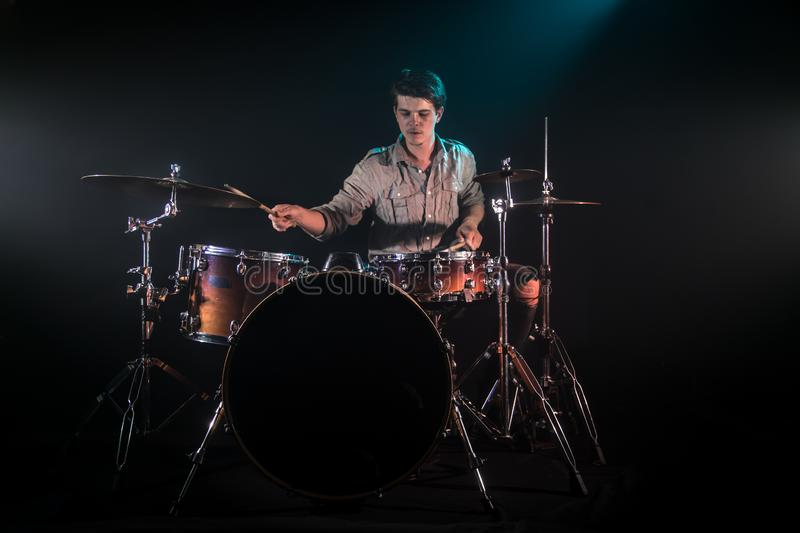 Musician playing drums, black background and beautiful soft light. Emotional play, music concept stock photos