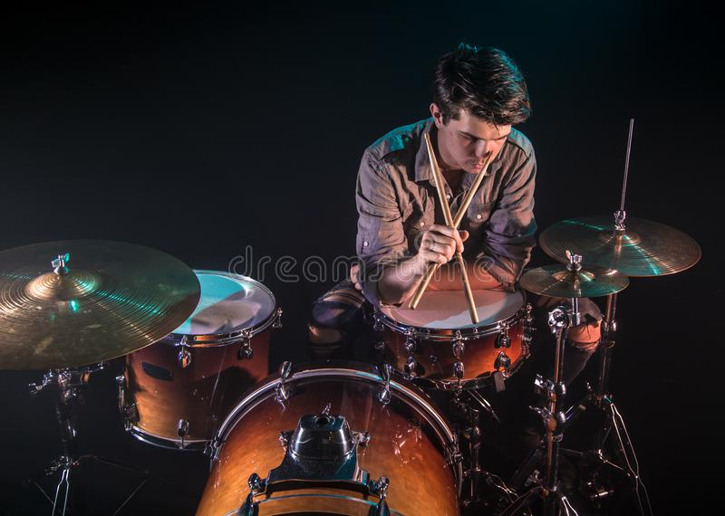 Musician playing drums, black background and beautiful soft light. Emotional play, music concept royalty free stock image