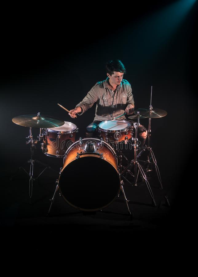 Musician playing drums, black background and beautiful soft light. Emotional play, music concept stock image