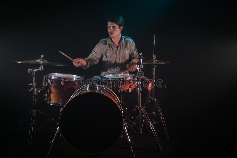 Musician playing drums, black background and beautiful soft light. Emotional play, music concept royalty free stock images