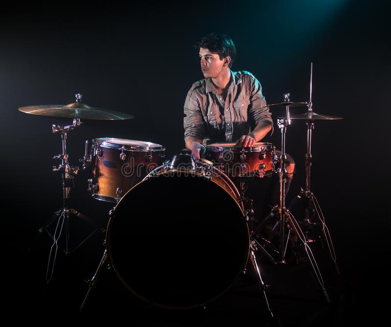 Musician playing drums, black background and beautiful soft light. Emotional play, music concept royalty free stock photo