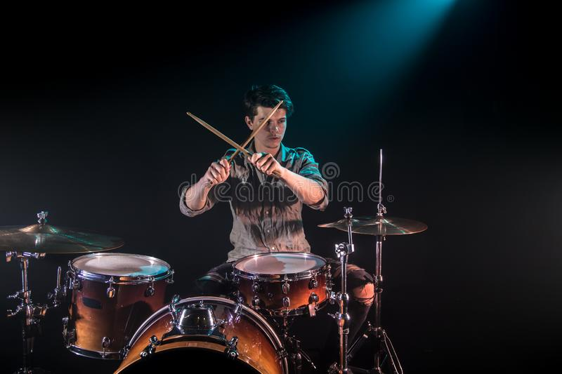 Musician playing drums, black background and beautiful soft light. Emotional play, music concept stock images