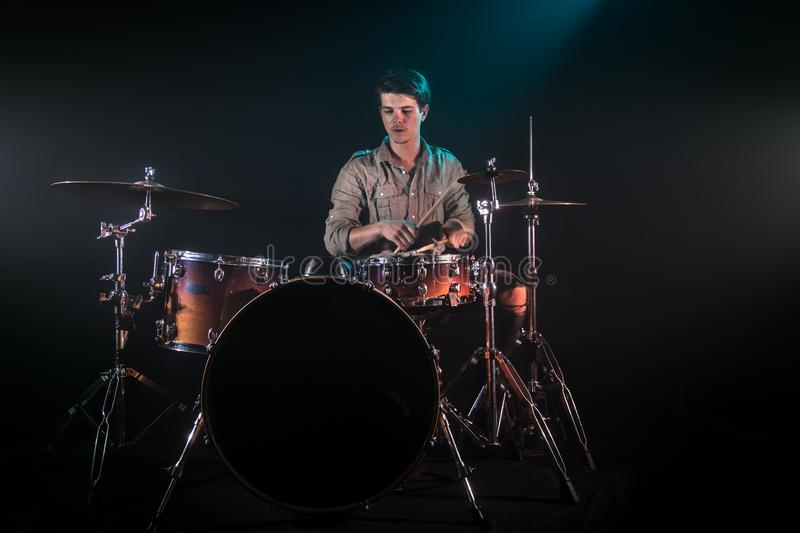 Musician playing drums, black background and beautiful soft light. Emotional play, music concept stock photography