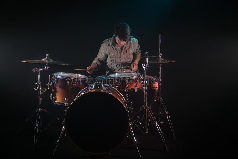 Musician playing drums, black background and beautiful soft light. Emotional play, music concept stock photo