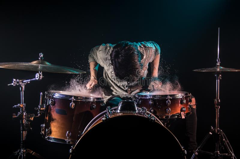 Musician playing drums with splashes, black background with beautiful soft light. Emotional play, music concept royalty free stock photos