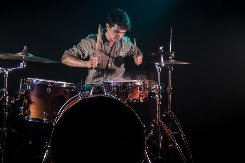 Musician playing drums with splashes, black background with beautiful soft light. Emotional play, music concept royalty free stock images