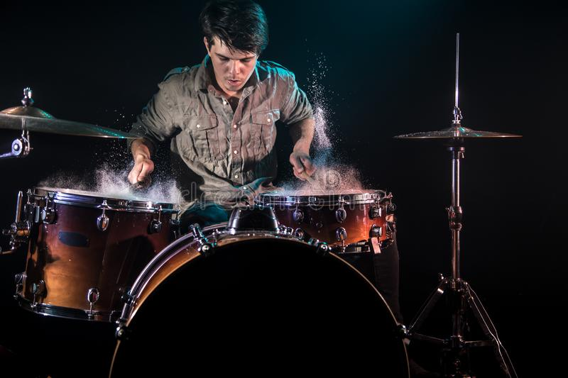 Musician playing drums with splashes, black background with beautiful soft light. Emotional play, music concept stock photos