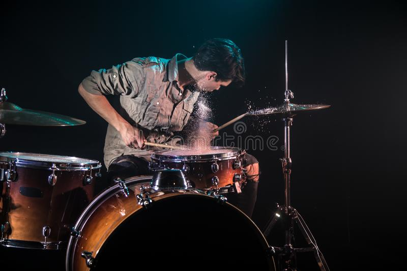 Musician playing drums with splashes, black background with beautiful soft light. Emotional play, music concept royalty free stock photography