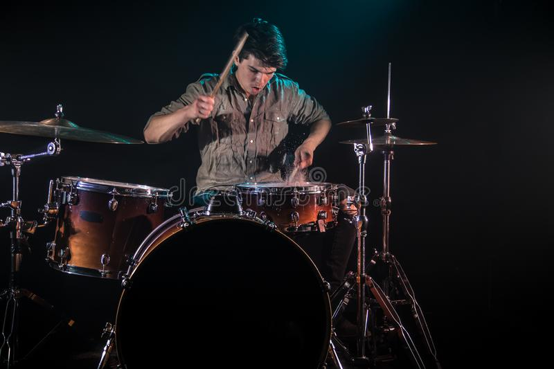 Musician playing drums with splashes, black background with beautiful soft light. Emotional play, music concept stock image