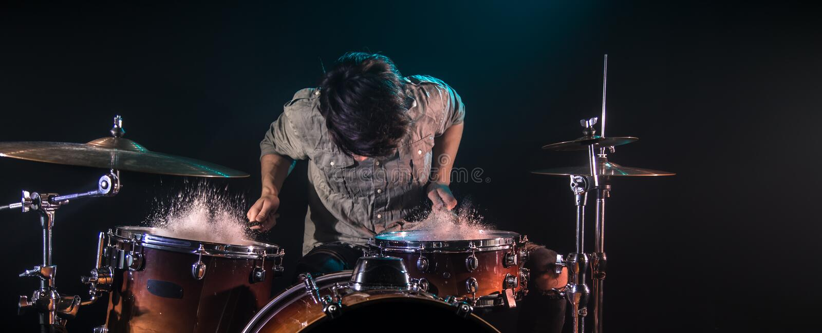Musician playing drums with splashes, black background with beautiful soft light. Emotional play, music concept royalty free stock image