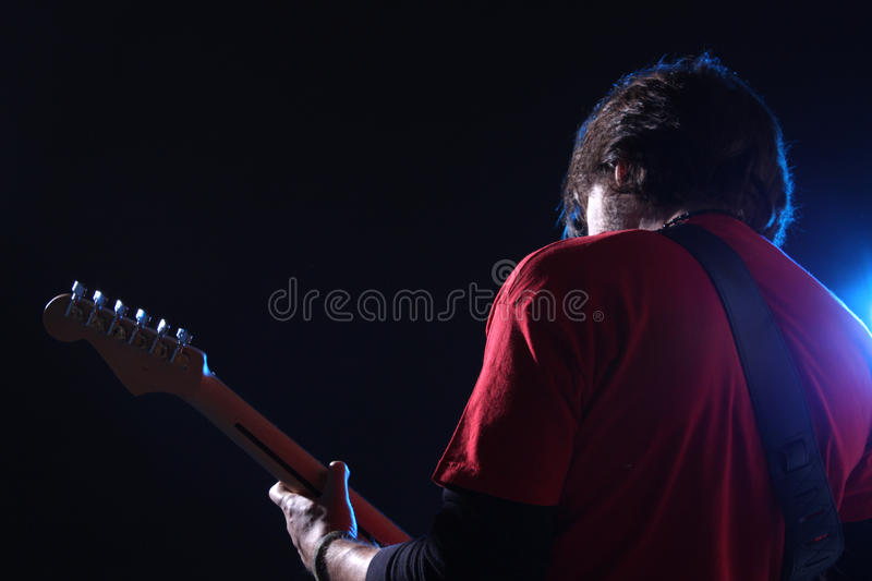 Musician playing electric guitar. On stage royalty free stock image