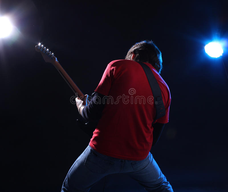 Musician playing electric guitar. On stage royalty free stock photo