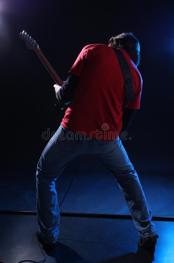 Musician playing electric guitar. On stage stock photo
