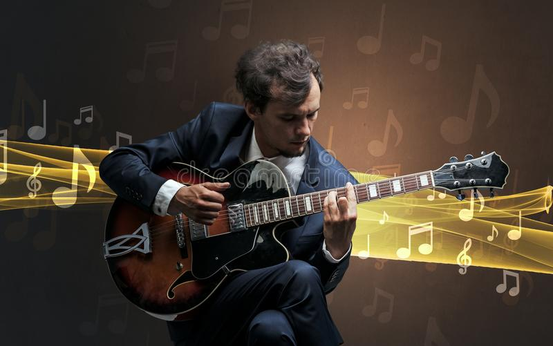 Musician playing on guitar with notes around. Young male musician playing on his guitar with musical notes around stock photo