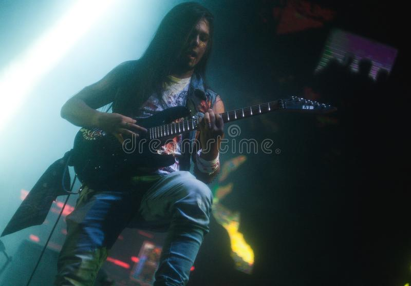 Musician playing guitar onstage stock photo