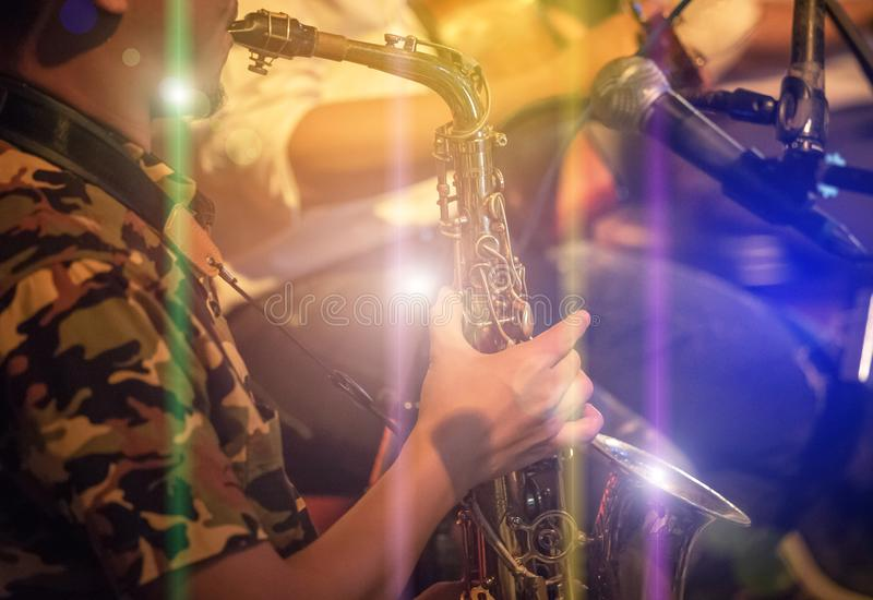 Musician playing the saxophone on band. In nigh concert stock photos
