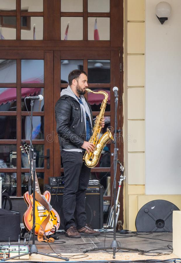 The musician playing the saxophone performs on the street in front of The State Philharmonics Sibiu - Thalia Concert Hall. Sibiu c royalty free stock photo