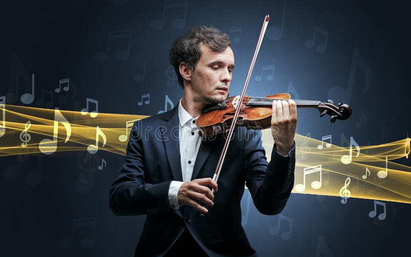 Musician playing on violin with notes around. Young male musician playing on his violin with musical notes around stock photography