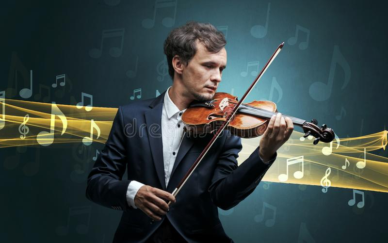 Musician playing on violin with notes around. Young male musician playing on his violin with musical notes around royalty free stock photo