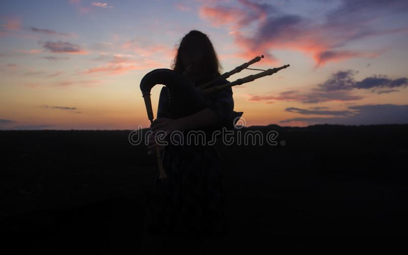 A musician plays the bagpipes in the fields at sunset royalty free stock photo