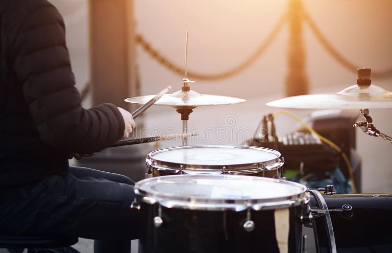 A musician plays with battered drumsticks on a drum set stock image