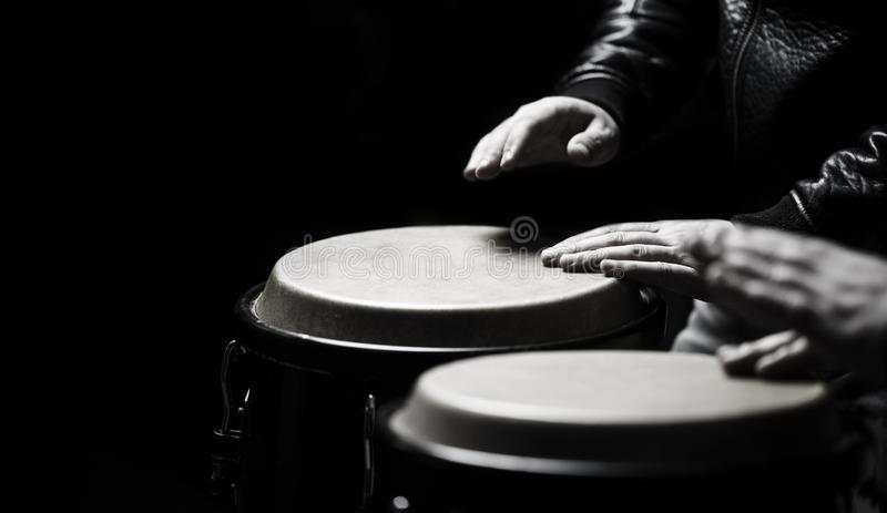 The musician plays the bongo. Close up of musician hand playing bongos drums. Afro-Cuba, rum, drummer, fingers, hand. Drum. Hands of a musician playing on bongs royalty free stock photos