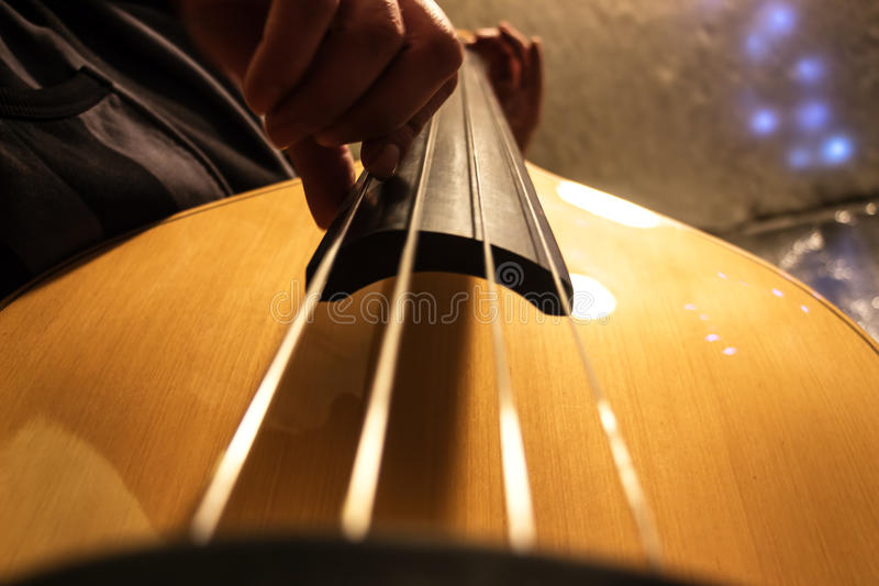 Musician plays the double bass. The musician plays the double bass. The light tone color of the bass. Bottom view royalty free stock image