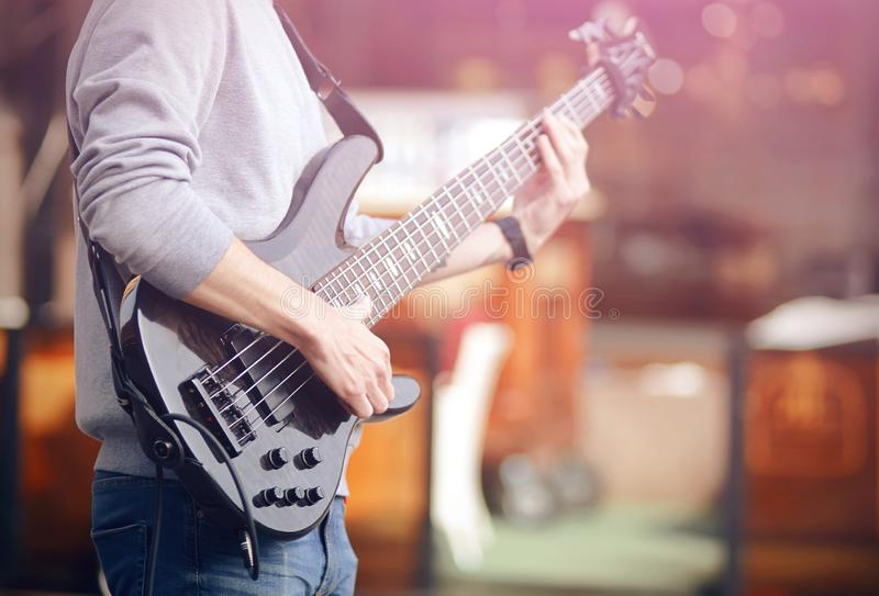 A musician plays a melody on a black bass electric guitar stock photography