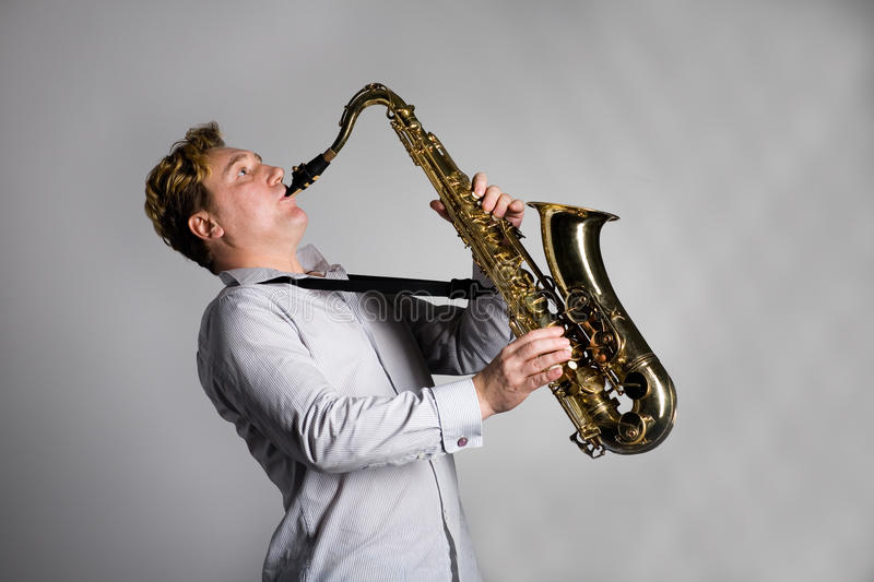 Musician plays the saxophone. Young musician plays the saxophone stock photography