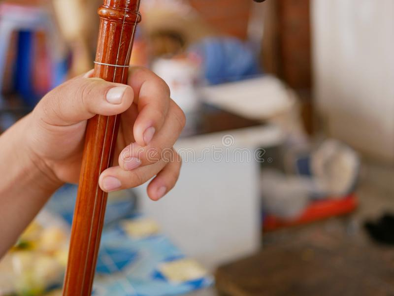 A musician`s hand playing Salor, two or three-string spike fiddle used in the Lanna region or in the North of Thailand. A musician`s hand playing Salor, two or stock image
