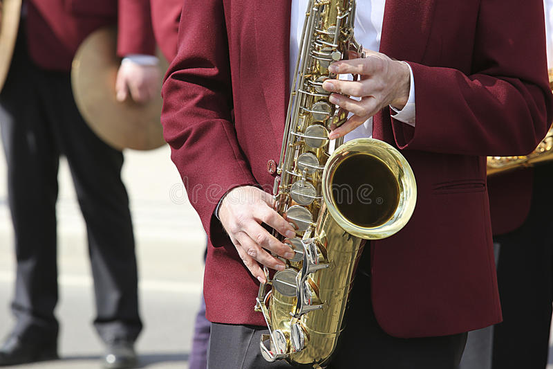 Musician with saxophone. Musician plays saxophone in the orchestra at the street stock photography