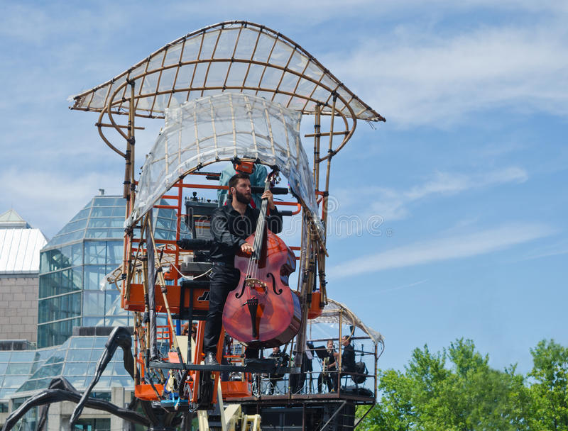 Musician up in the air playing a Double Bass instrument. Making its debut in North America, La Machine wanders around public spaces, in Ottawa, Canada. It is