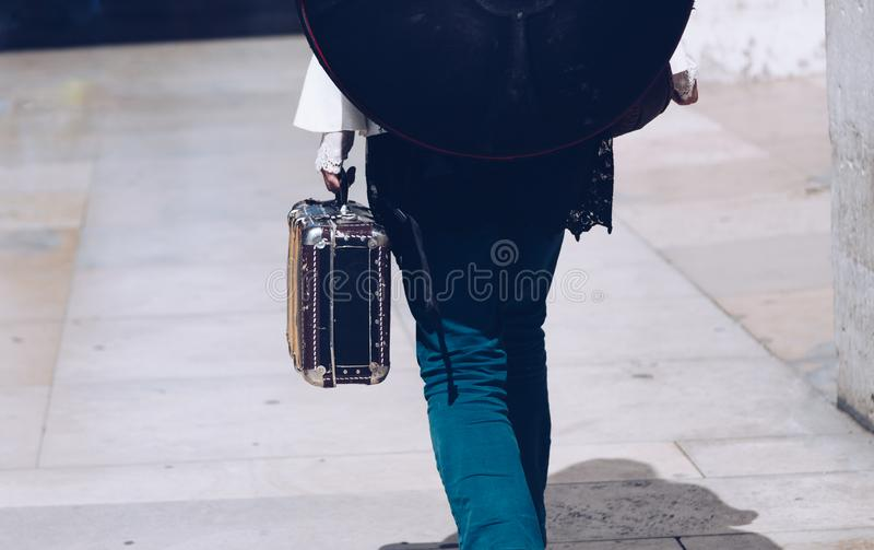 Musician with vintage suitcase walking away - street artist - traveling around the world. royalty free stock photos