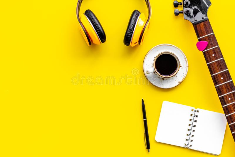 Musician work place with guitar, earphones, notebook and coffee on yellow background top view mock up royalty free stock image