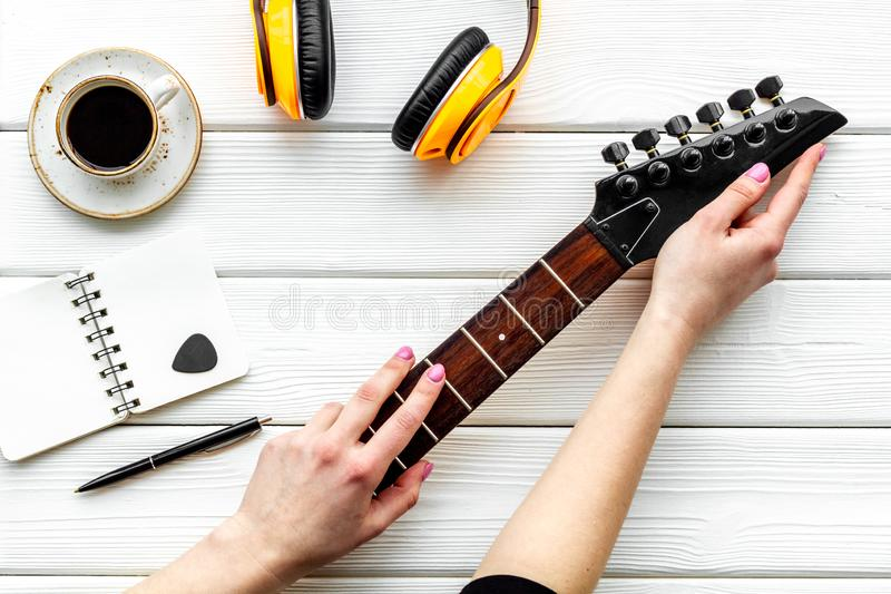 Musician work place with guitar, earphones, notebook and coffee on white wooden background top view stock photography