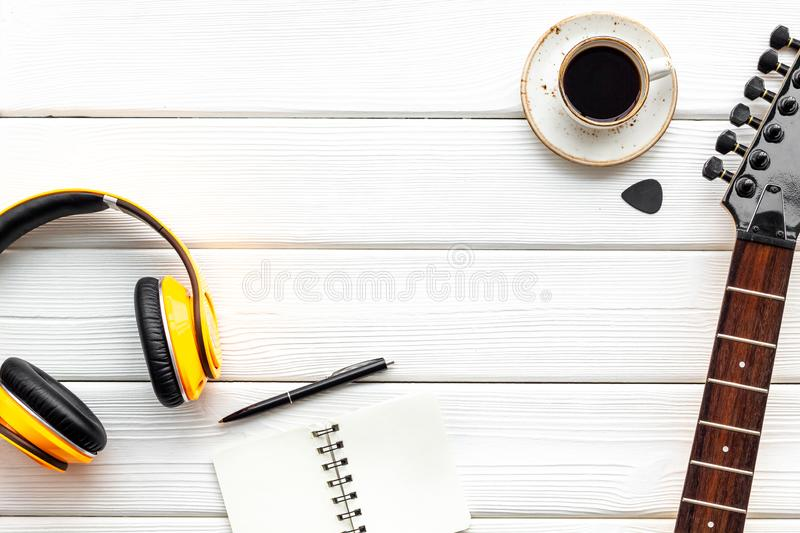 Musician work place with guitar, earphones, notebook and coffee on white wooden background top view mock up stock photography