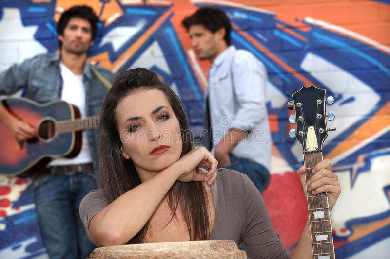 Musicians by a tagged wall stock image