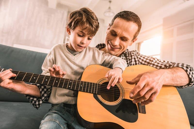 Musicien adulte capable critiquing la manière de son fils de jouer la guitare photos stock