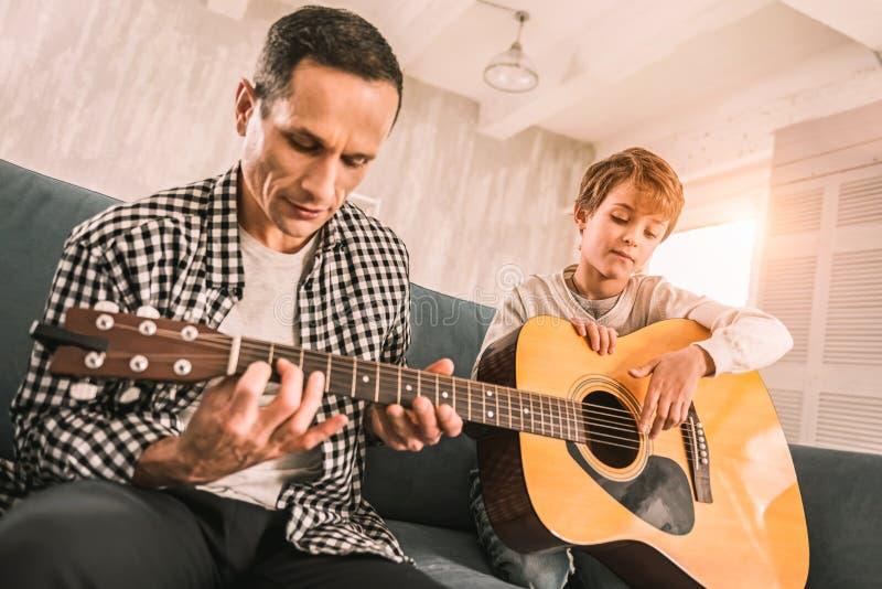 Musicien adulte professionnel ajustant les ficelles sur sa guitare photo stock