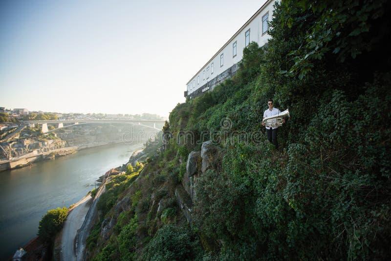 Musicien avec le tuba devant la rivière de Douro de Porto image libre de droits