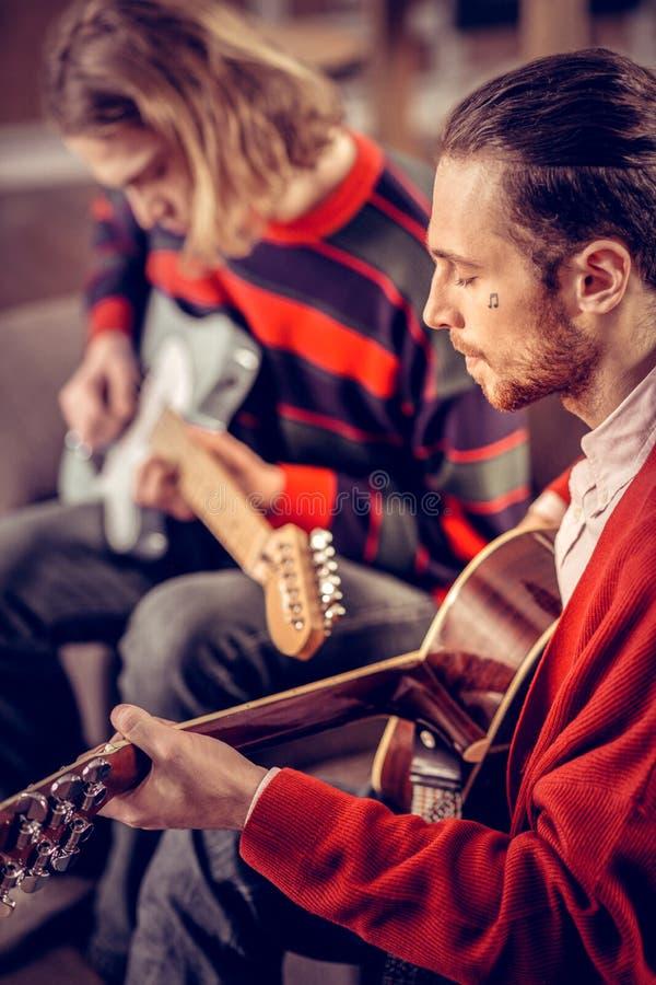 Musicien avec peu de tatouage sur son visage jouant la guitare photographie stock libre de droits