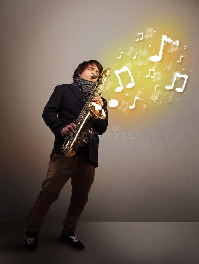 Musicien beau jouant sur le saxophone avec les notes musicales photo libre de droits